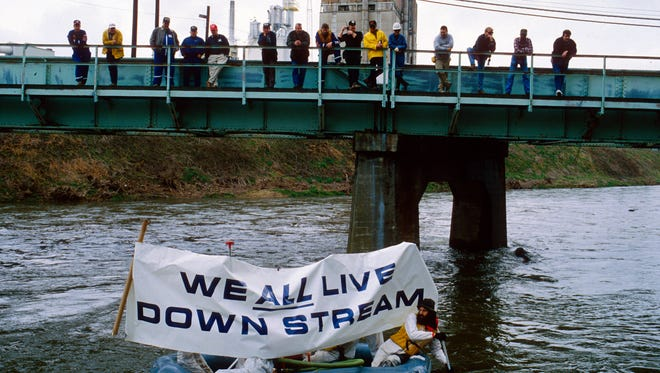 Environmental activists carry their message by raft past the Champion International paper mill to protest pollution of the Pigeon River on Saturday, March 27, 1993, in Canton, N.C. The state of North Carolina is now considering loosening regulations on effluent entering the Pigeon River from a paper product plant in Canton, N.C.