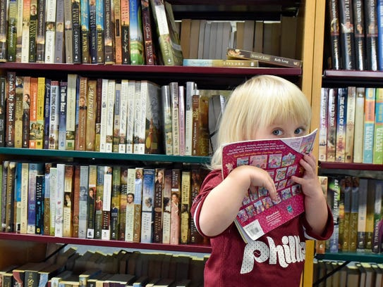 Two-year-old Lillian Schultz looks over books Thursday,