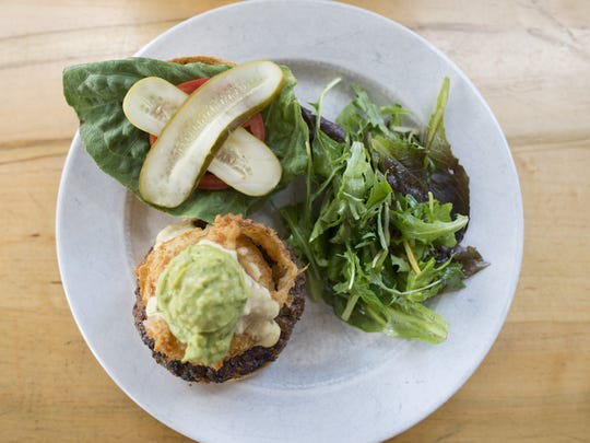 "The ""Ultimate Supreme Mega Burger"" is served with a helping of greens at Tasty Harmony on Thursday, June 22, 2017. The vegetarian and vegan restaurant, located at 160 W. Oak Street, serves the burger with a soy, bean and rice patty."