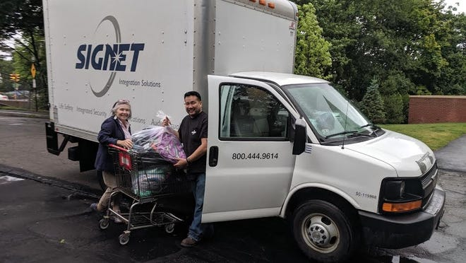 Eileen Kelly, Interfaith Social Services' food pantry manager, accepts a donation of backpacks and supplies from a Signet Electronics employee during Interfaith's 2019 Backpack Drive.
