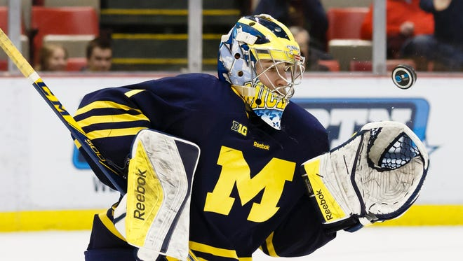 Michigan's Steve Racine (1) makes a save in the third period against  Minnesota during an NCAA college hockey game in the Big Ten Conference tournament Saturday, March 21, 2015, in Detroit.