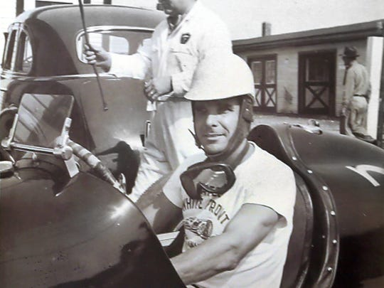 George Robson, winner of the 1946 Indianapolis 500, sits in his race car, wearing a Mates' White Front T-shirt. In the 1950s and 1960s, some of the drivers in the Indianapolis 500 wore those T-shirts around the track, which were given to them by Nick Mates, who along with his brother Mike Mates ran the restaurant and bar by that name, located down the road from the Speedway, at 3535 W. 16th Street. Mates told the race car drivers and mechanics that if he saw them wearing the T-shirts around the Indianapolis Motor Speedway, he would give them a free lunch.