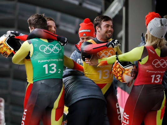 Natalie Geisenberger, Johannes Ludwig, Tobias Wendl and Tobias Arlt of Germany celebrate in the finish area after winning the gold medal after the luge team relay at the 2018 Winter Olympics in Pyeongchang, South Korea, Thursday, Feb. 15, 2018. (AP Photo/Andy Wong)