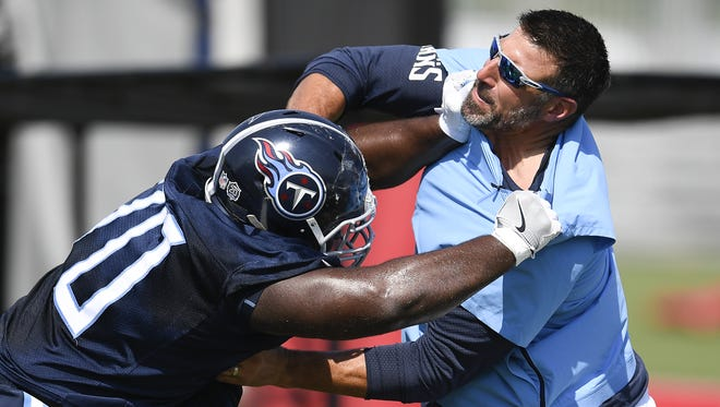 Titans coach Mike Vrabel works with defensive tackle Mike Ramsay (70) during practice July 26.