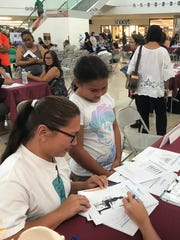 Ashley Rosario and her daughter Amari, 9, receive health information handouts at the Guam Regional Medical City health fair at the Micronesia Mall on July 23, 2017.