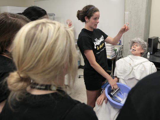 Second-semester nursing student Emily Greis demonstrations how to administer a feeding tube through the nostril of a lifelike dummy.