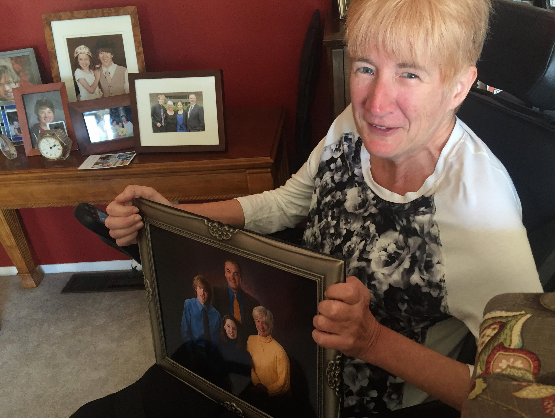 Pam Hillery holds a family portrait in her Havre home.