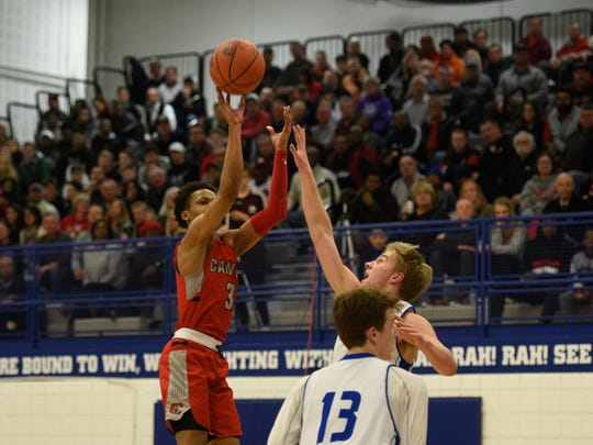 Canton's B. Artis White launches the jump shot against Catholic Central in the district opener.