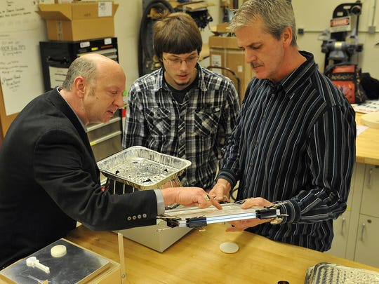 Mark Mattern of Butler County Community College's Hospitality Program, left, sophomore Mike Paul, center, and engineering tech professor Mike Aikens review detail from a vacuum mold in the school's manufacturing lab.