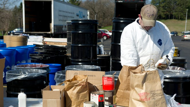 A worker sorts through bags at a Battle Creek recycling event in 2013.