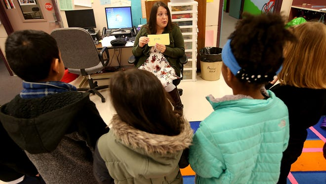 Stephanie Codorniz goes over vocabulary words with her before school reading group at West Hills STEM Academy in Bremerton.