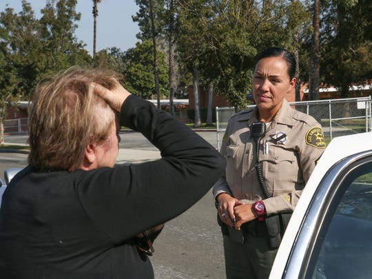 Los Angeles County Sheriff's deputy Joanne Arcos talks with Vicki Clark, whose family members have been in legal trouble because of drug use, just outside of her home in Hacienda Heights, Calif., November 23, 2016.