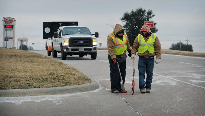 It was cold work for Joe Munoz, left, and Ivan Morales of MasTec measure as they marked off an area along the I-44 access road Friday. Crews will be laying fibre optic communications cable in the area in the future.