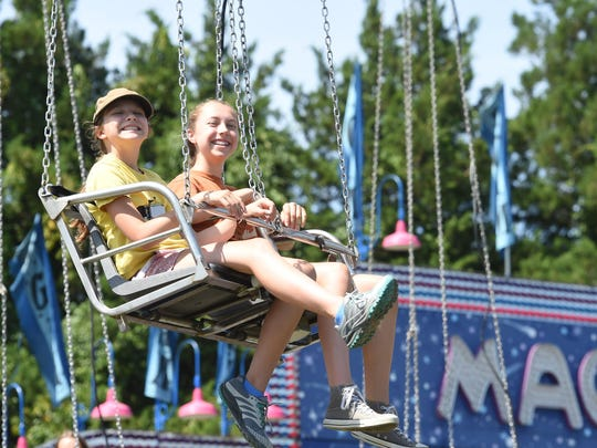 From left, Josie and Abbey Gravatt of Gardiner smile as the Vertigo Swing comes to a stop at Dutchess County Fair in Rhinebeck on Saturday.