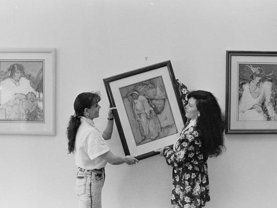 A photo from April 1991 shows Amy Burnett hanging images in her gallery after she purchased the building in downtown Bremerton.