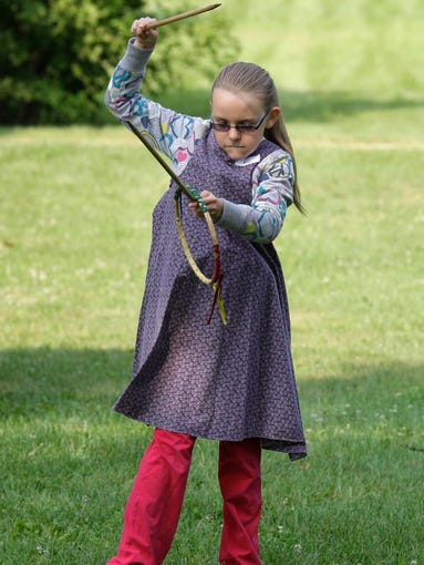 Erin Haase, 10, of Plymouth works to figure out the 1860s game Graces Tuesday July 29, 2014 at the Wade House in Greenbush. The game Graces was developed in France and was touted as a game to make young girls more graceful.