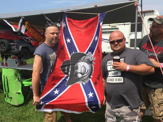 Olais Moss, left, of Bloomingdale; Danny Landis, center, of Allegan; and Gary Comstock, 45, of Allegan, display their flag at their campsite.