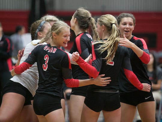 The SPASH volleyball team celebrates a point at Stevens Point Area Senior High School, Tuesday, Aug. 25, 2015.