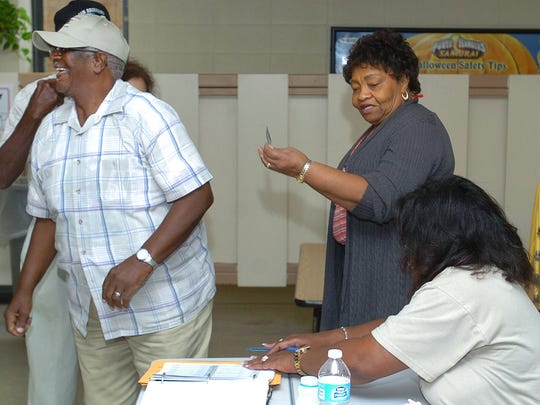 Photo ID's are checked by voting commissioners as voters cast their vote Saturday at Ward 1 Precinct 29.