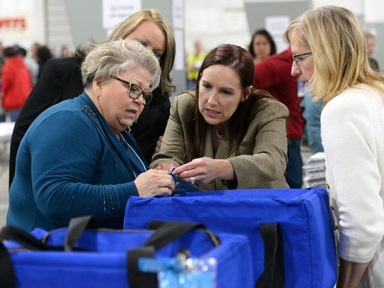 Ingham County Clerk Barb Byrum, center, helps two recount