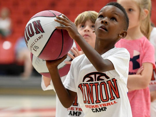 Carmelo Tyler looks up as he concentrates on making a basket during the Union University pee wee summer basketball camp, Monday, June 5.