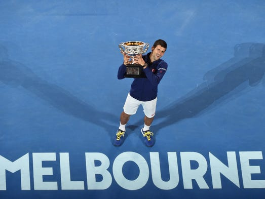 Novak Djokovic holds The Norman Brookes Trophy after