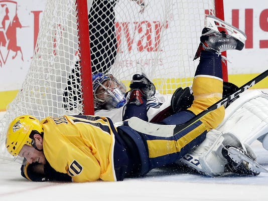 Nashville Predators center Colton Sissons (10) and Colorado Avalanche goalie Semyon Varlamov, of Russia, lie on the ice after Sissons scored a goal and collided with Varlamov in the second period of an NHL hockey game Tuesday, Oct. 17, 2017, in Nashville, Tenn. (AP Photo/Mark Humphrey)