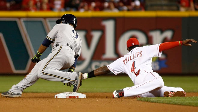 Milwaukee Brewers shortstop Jean Segura (9) is safe at second beating the tag from Cincinnati Reds second baseman Brandon Phillips (4) in the seventh inning at Great American Ball Park.