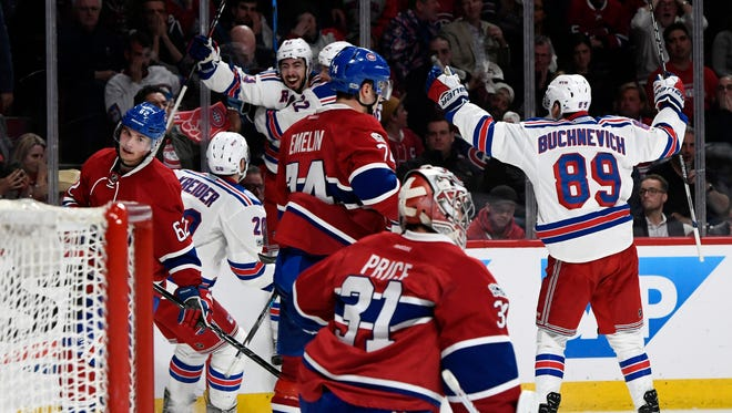 The New York Rangers celebrate their winning goal in overtime against the Montreal Canadiens.