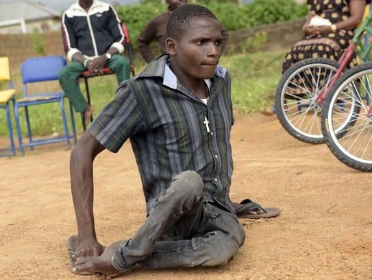 Polio survivors Gabriel Christopher crawls to his new