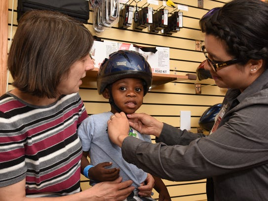 Jayden Boles tries on a bike helmet with his grandma