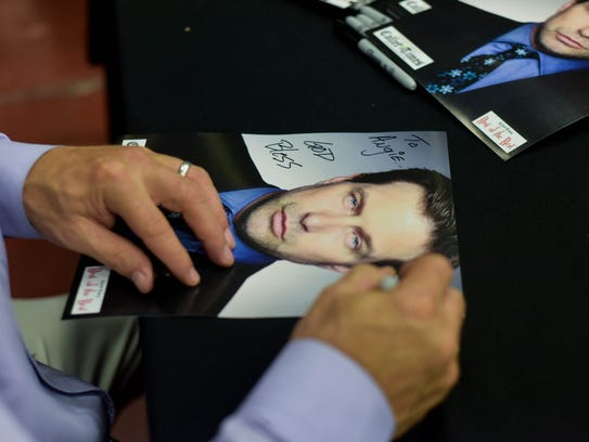 Stephen Baldwin signs a photo for a fan during the