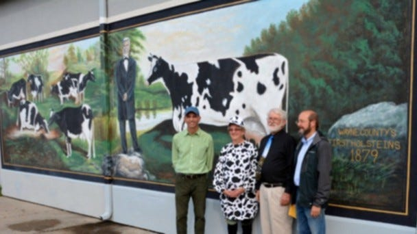 Gene Bavis, second from right, stands in front of a Walworth mural completed in 2013.