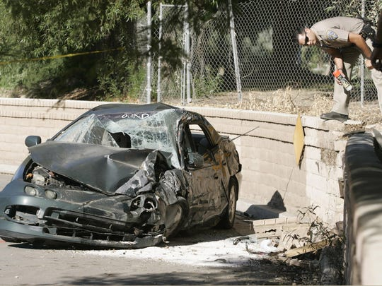 A CHP officer surveys the scene of a fatal crash in a Palm Springs police pursuit on Nov. 15, 2005. The driver, Fred Ray Bradley Jr., was killed.