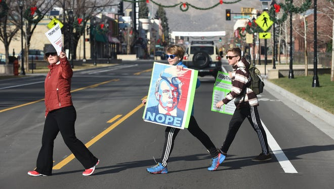 Protesters cross the street in front of the Nevada Capitol during the Electoral College votes on Monday.