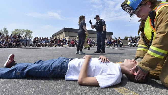Gibraltar High School student Evan Henry plays an injured passenger of a two-car collision during a mock crash drill involving drinking and driving Thursday. Completing the sobriety test in background is student Alexis Lessman, who failed the test and was handcuffed at the scene. The mock crash unfolded in front Gibraltar students from grades nine through 12.