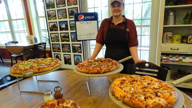 Ashley Reigle, a cook at North Star Pizzeria and Restaurant, stands next to the four sizes of pizza available at North Star.