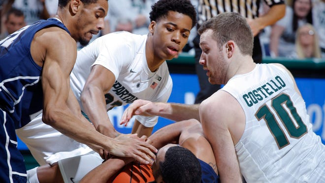 Penn State's Isaiah Washington, left, and Shep Garner (33) and Michigan State's Matt Costello (10) and Deyonta Davis wrestle for the ball Sunday, Feb. 28, 2016, in East Lansing.