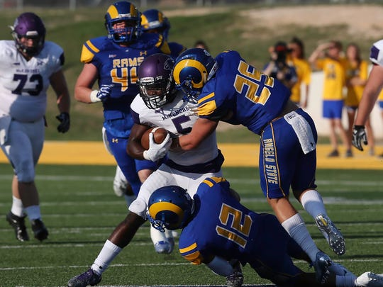 The Rams defensemen Kaimon Ontiveros (12) and Leddy French (25) takes down Derrick Curry (5) of the McKendree Bearcats.