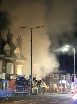 Emergency personnel attend the scene of an incident in Leicester, central England, Sunday Feb. 25, 2018. Four people were hospitalized in critical condition following an explosion that left a building in the English city of Leicester in flames Sunday, local emergency agencies said.