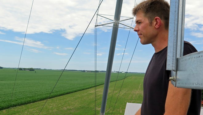 Scott Haase, a farmer in Blue Earth, Minn., looks out at a field where he planted cover crops between rows of corn on July 5, 2017.  Miles from the farmers markets, craft breweries and farm-to-table restaurants of the Twin Cities, more traditional farmers are thriving in the Midwest. Corn and soybean farmers face heightened expectations for environmental stewardship and want to build healthy soils that can withstand heat, drought and heavy rain.