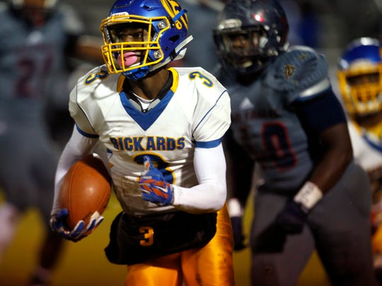 Rickards' Marcus Riley scrambles out of the pocket against Wakulla during their playoff game on Friday.