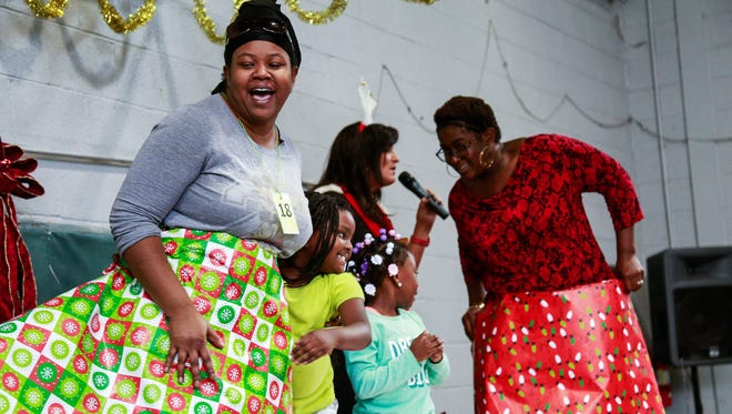 Kendra Myers and daughter Lilliunna Myers participate in the wrapping paper contest during Christian Services' Birthday Party for Jesus on Saturday.