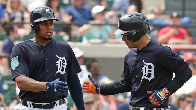 Detroit Tigers' Jose Iglesias, right, gets a high five from teammate Jeimer Candelario after scoring a run in the fifth inning against the Atlanta Braves, Sunday, March 11, 2018 in Lakeland, Fla.