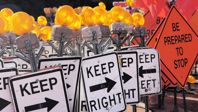 Road construction safety signs including black white keep right reflectors and orange be prepared to stop warnings.