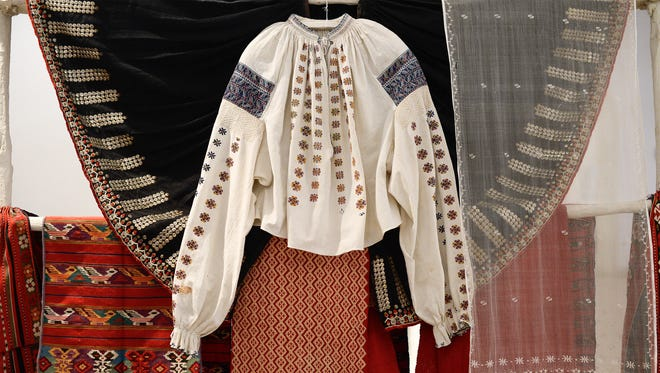 An ancient peasant's blouse with its distinctive stitching on display alongside other hand woven carpets and pieces of clothing at the Romanian Peasant Museum, in Bucharest, Romania, Tuesday, Oct. 24, 2014.