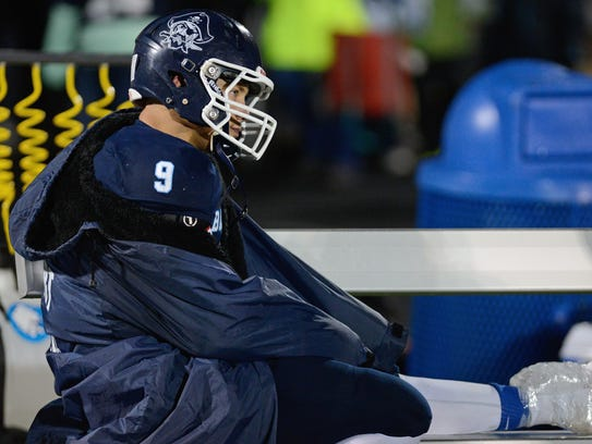 Bay Port quarterback watches from the bench while icing