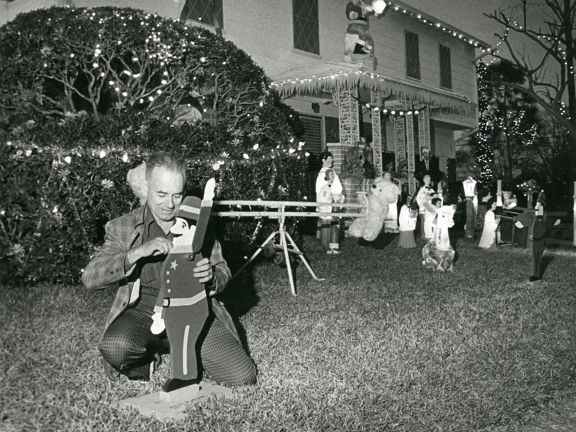 Billy Aldridge adjusts one of the multitude of Christmas decorations in his yard at the corner of Delaine Drive and Doddridge Street in 1980.