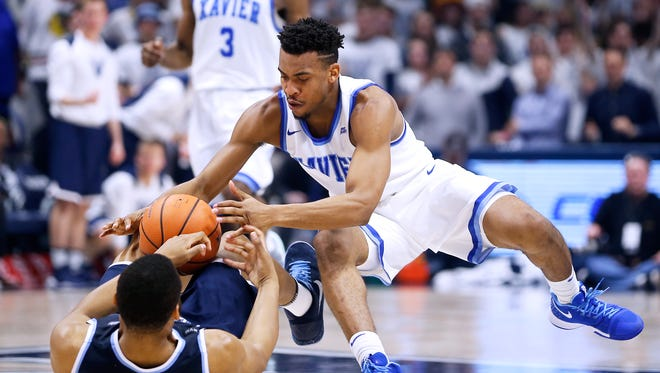 Xavier Musketeers guard Paul Scruggs (1) and Villanova Wildcats forward Omari Spellman (14) battle for a loose ball during the 2nd half at the Cintas Center Saturday Feb. 17, 2018. Xavier lost 95-79.