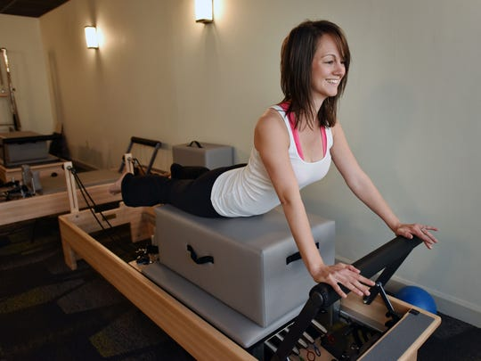 Instructor Rachel May demonstrates reformer Pilates at Fitness Plus on Old Square Road in Jackson.